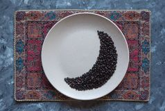 Coffee beans in moon shape on a plate. Ramadan concept royalty free stock image