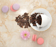 Coffee beans in mug, flower cookies and French macarons. top vie Royalty Free Stock Images