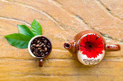 Coffee beans in a mug & kettle. Coffee beans in a mug & kettle with flower and leaves top view Royalty Free Stock Photo