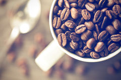 Coffee beans in mug Stock Image