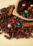 Coffee beans, multicoloured drops, cinnamon and vanilla. Ingredients for making a drink Stock Photo