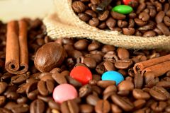 Coffee beans, multicoloured drops, cinnamon and vanilla. Ingredients for making a drink Stock Photography