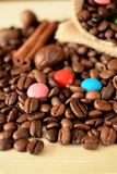 Coffee beans, multicoloured drops, cinnamon and vanilla. Ingredients for making a drink Royalty Free Stock Photography