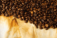 Coffee beans on old paper. Roasted coffee beans on old burned paper Royalty Free Stock Image