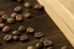 Coffee beans on old vintage open book. Menu, recipe, mock up. Wooden background. Stock Images