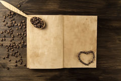 Coffee beans on old vintage open book. Menu, recipe, mock up. Wooden background. Royalty Free Stock Photography