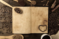 Coffee beans on old vintage open book. Menu, recipe, mock up. Wooden background. Royalty Free Stock Images