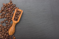 Coffee beans and olive wood scoop on black background of slate or stone background with copy space. Stock Images