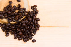 Coffee beans over the wood plate. On the brown background royalty free stock photo