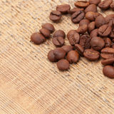 Coffee beans over wooden table - close up shot Royalty Free Stock Photos