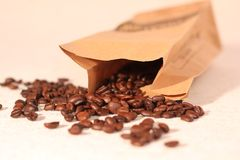 Coffee beans overflowing from paper bag Stock Photography