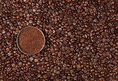 Coffee Beans. Overhead view of a bowl of ground coffee on a roasted whole, unground coffee bean background royalty free stock photography