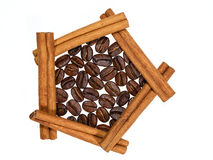 Coffee beans in pentagon of cinnamon sticks. Roasted coffee beans in pentagon of cinnamon sticks on white background royalty free stock photography