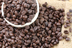 Coffee beans placed on bag sack and white cup. Stock Photos