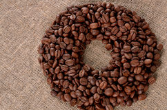 Coffee Beans. Placed in shape of bean on burlap background stock photo