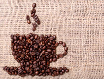 Coffee Beans, placed in shape of cup on linen or burlap Royalty Free Stock Photography