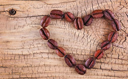 Coffee beans placed in shape of heart on old wooden Stock Image