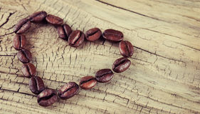 Coffee beans placed in shape of heart on old wooden Royalty Free Stock Photography