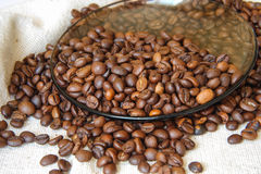 Coffee beans on a plate. Plate and a bag of coffee beans Stock Photo