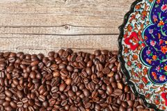 Coffee beans and a plate with a beautiful Turkish ornament royalty free stock photos