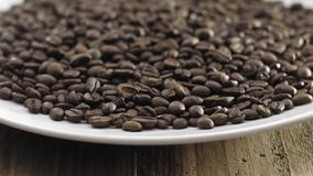 Coffee beans on plate closeup. 4K stock video