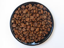 Coffee beans on the plate over white background. A lot of coffee beans on the black plate over white background stock photography