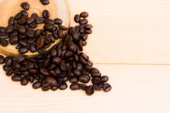 Coffee beans and the plate. Coffee beans over the wood plate on the brown background stock photos