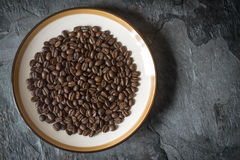 Coffee beans on the plate on the stone table top view Royalty Free Stock Photography