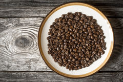 Coffee beans on the plate on the wooden table top view Stock Image