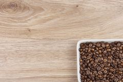 Coffee beans in a porcelain bowl on wooden background Royalty Free Stock Photo
