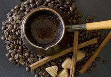 Coffee beans, Pots, cinnamon on dark background Stock Photos