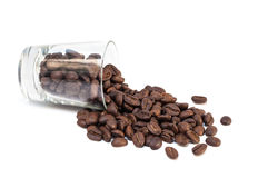 Coffee beans pour out from glass shot Royalty Free Stock Photo