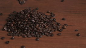 Coffee beans pour out on a wooden table, slow motion. stock video footage