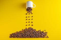 Coffee beans are poured from cup in pile on yellow background. Conceptual photo Stock Images