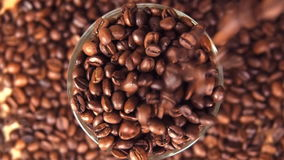 Coffee beans are poured into a glass beaker close up. Grains are poured over the edge. stock footage