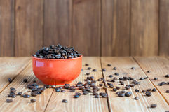 Coffee beans in red bowl on dark wooden background Royalty Free Stock Image