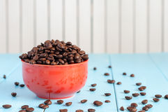 Coffee beans in red bowl on light wooden Royalty Free Stock Photo