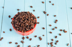 Coffee beans in red bowl on light wooden Royalty Free Stock Photography
