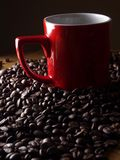 Coffee beans and a red coffee mug Stock Photos