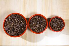 Coffee Beans in red cup. Coffee beans in three red cups on a wood grain table Royalty Free Stock Photography
