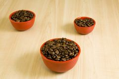 Coffee Beans in red cup. Coffee beans in three red cups on a wood grain table Stock Photography