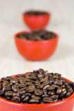 Coffee Beans in red cup. Close up of coffee beans in three red cups on a wood grain table Stock Photos