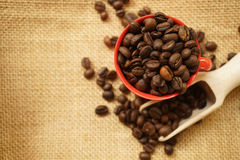 Coffee beans and the red cup on gunny bag. For background Royalty Free Stock Images