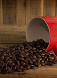 Coffee beans and red cup on the wooden table, Concept filter sep Royalty Free Stock Images