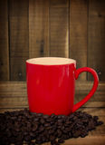 Coffee beans and red cup on the wooden table, Concept filter sep Royalty Free Stock Photography