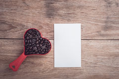 Coffee beans in red heart plastic cup on wooden table top view Royalty Free Stock Images