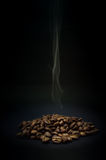 Coffee beans with rising steam on black background royalty free stock image