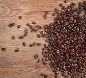 Coffee Beans. Roasted whole, unground coffee beans spilled on a wooden background stock images