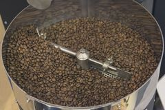 Coffee beans during the roasting process inside the hopper drum. Type roaster Royalty Free Stock Photo