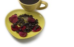 Coffee with beans and rose on a heart shaped plate. Valentine's royalty free stock image